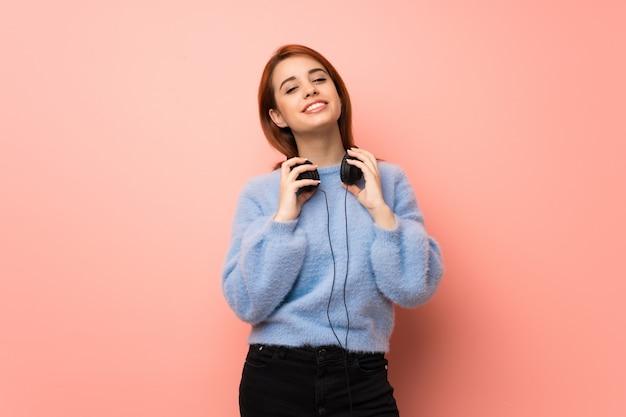 Jeune femme rousse sur rose avec un casque Photo Premium