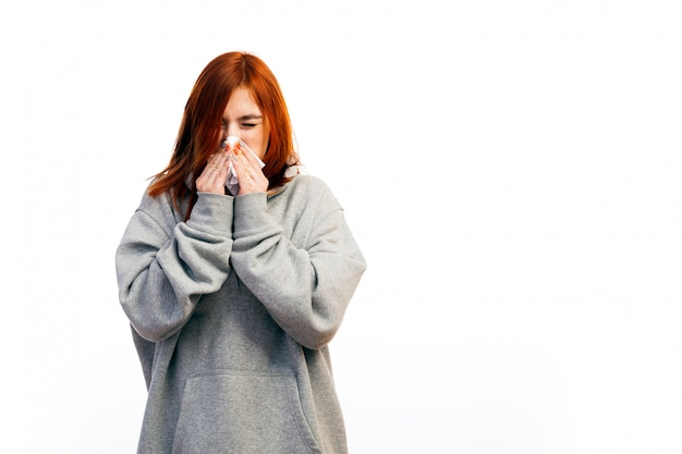 Une jeune femme rousse en sweat-shirt gris est tombée malade d'un rhume, a fermé les yeux et a éternué Photo Premium