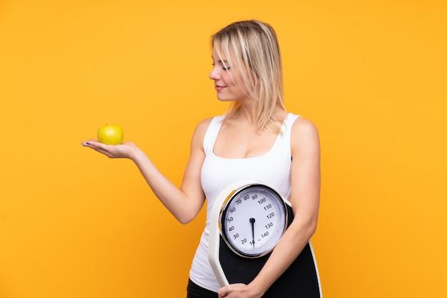 Jeune Femme Russe Blonde Sur Mur Jaune Isolé Tenant Une Machine De Pesage Tout En Regardant Une Pomme Photo Premium