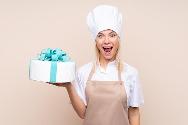 Jeune Femme Russe Avec Un Gros Gâteau Avec Surprise Et Expression Faciale Choquée Photo Premium