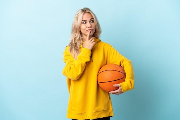 Jeune Femme Russe Jouant Au Basket-ball Isolé Sur Mur Bleu Ayant Des Doutes Tout En Regardant Photo Premium