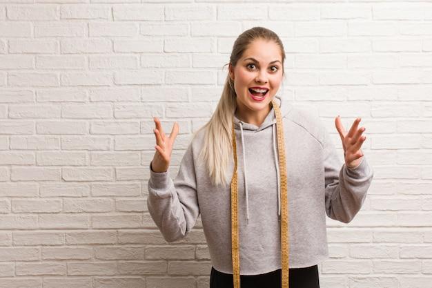 Jeune femme russe de remise en forme tenant un ruban de mesure Photo Premium