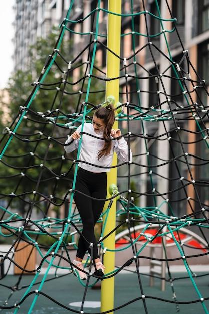 Jeune Femme S'amusant Sur La Pyramide De Corde Sur L'aire De Jeux Photo gratuit