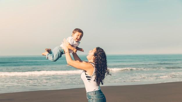 Jeune femme s'amuser avec bébé sur la plage d'été Photo gratuit