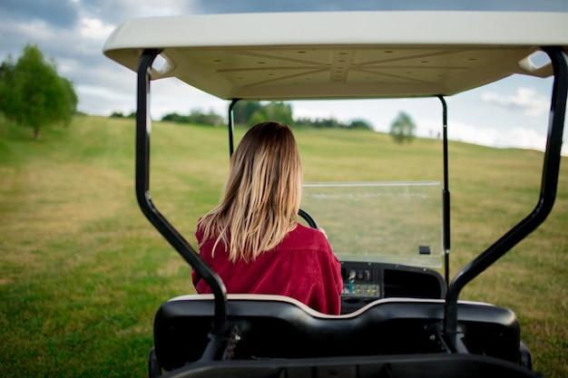 Jeune femme s'amuser avec une voiture de golf sur un champ en montagne Photo Premium