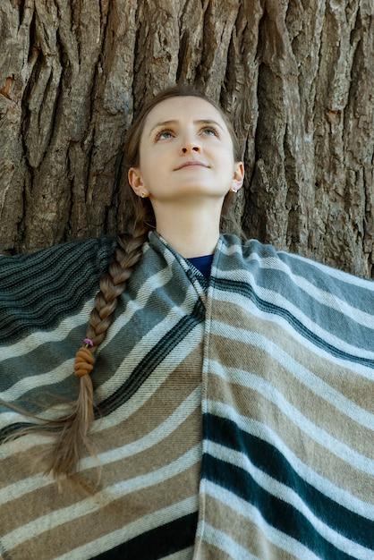 La jeune femme s'appuya contre le tronc d'un grand arbre. unité avec la nature Photo Premium