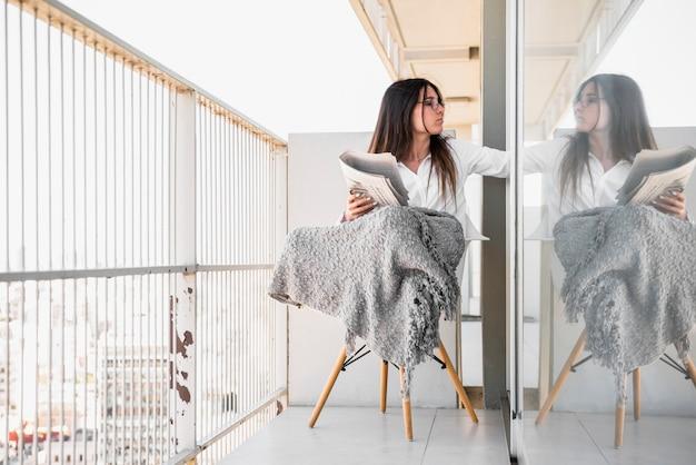 Jeune femme, s'asseoir chaise, sur, balcon, journal lisant Photo gratuit