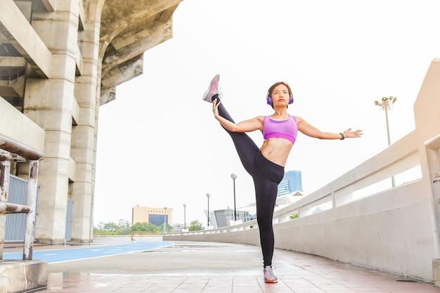 Une jeune femme s'étire ou réchauffe son corps comme l'une des postures de yoga Photo Premium