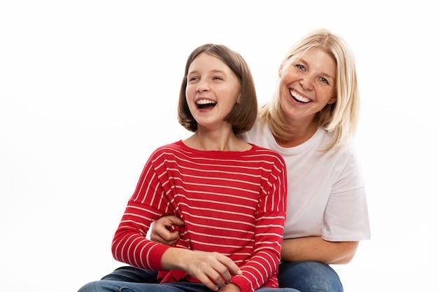 Jeune Femme Avec Sa Fille Adolescente Câlins Et Riant. Mur Blanc. Photo Premium