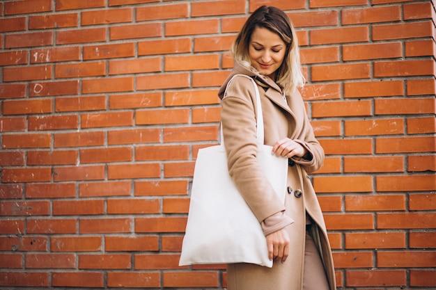 Jeune femme avec un sac près du mur de briques Photo gratuit