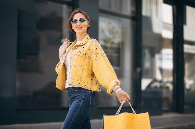 Jeune femme avec des sacs dans la ville Photo gratuit