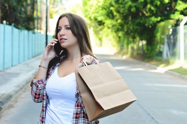 Jeune femme avec des sacs à provisions à l'aide de smartphone Photo Premium