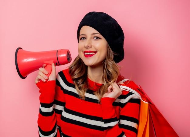 Jeune femme avec des sacs à provisions et haut-parleur sur mur rose Photo Premium