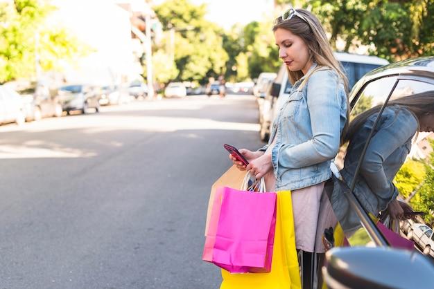 Jeune Femme Avec Des Sacs De Shopping Lumineux à L'aide De Smartphone En Voiture Photo gratuit