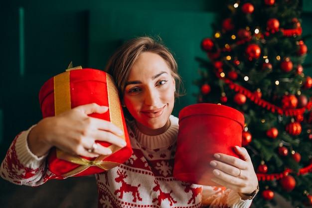Jeune femme avec sapin de noël tenant des boîtes rouges Photo gratuit