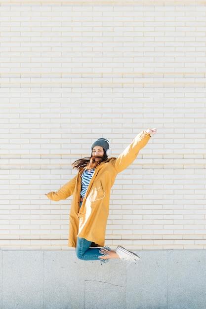 Jeune femme sautant contre le mur de briques avec casque Photo gratuit