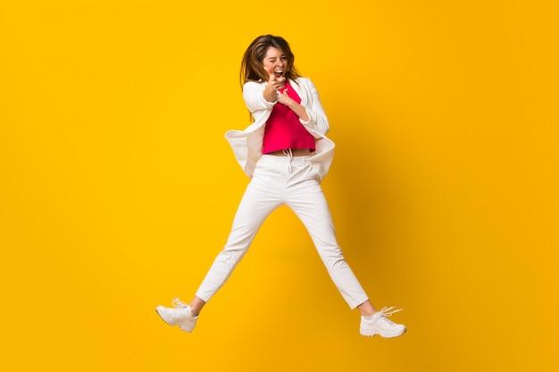 Jeune femme sautant par-dessus un mur jaune isolé pointant vers l'avant Photo Premium