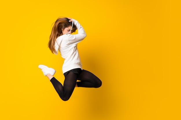 Jeune femme sautant par-dessus un mur jaune isolé Photo Premium