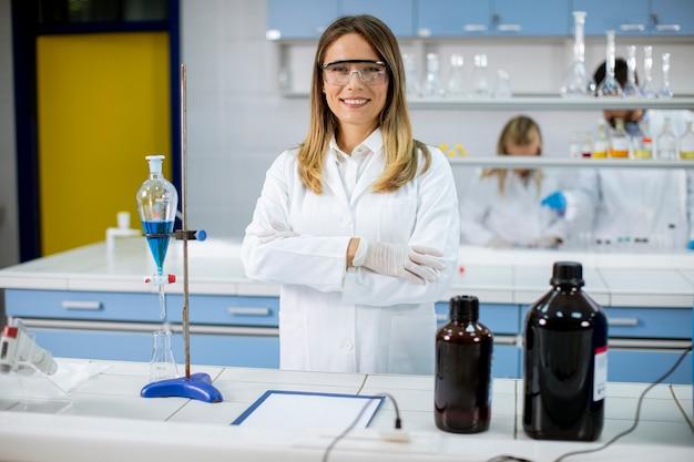 Jeune Femme Scientifique En Blouse Blanche Debout Dans Le Laboratoire Biomédical Photo Premium