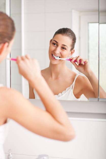 Jeune femme se brosser les dents au lavabo Photo Premium