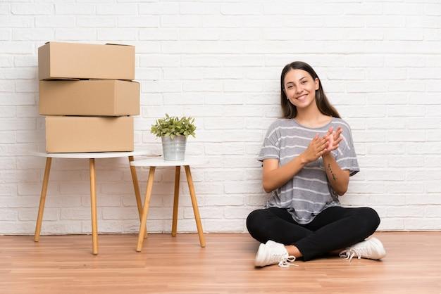 Jeune femme se déplaçant dans la nouvelle maison parmi les boîtes applaudissant Photo Premium