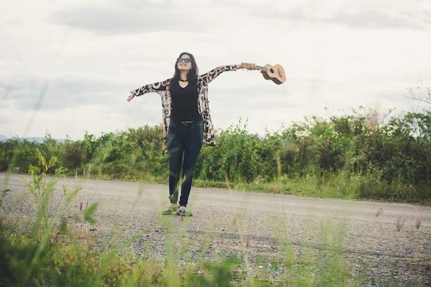 Jeune femme se détendre ukulélé brun de pentecôte dans le parc. Photo Premium