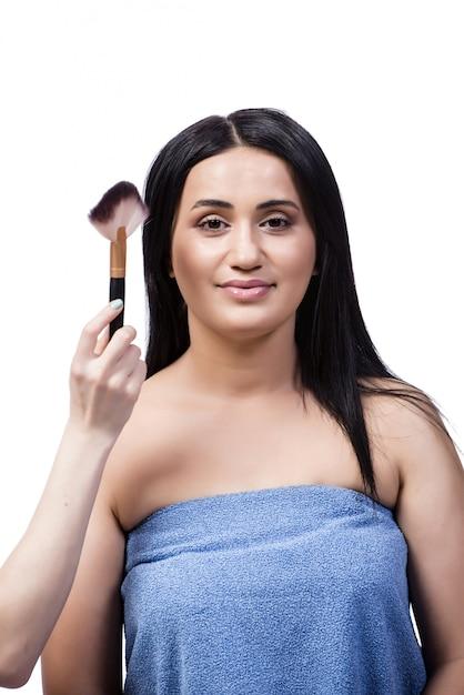 Jeune femme se maquillage isolé sur blanc Photo Premium