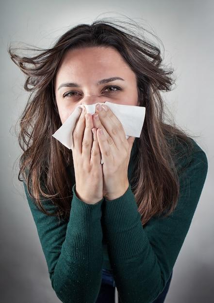 Jeune femme se moucher avec un mouchoir en papier. Photo Premium