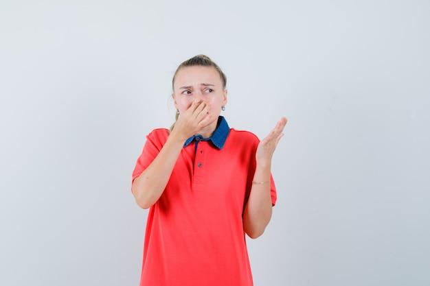 Jeune Femme Se Pinçant Le Nez En Raison D'une Mauvaise Odeur En T-shirt Et à L'air Dégoûté Photo gratuit