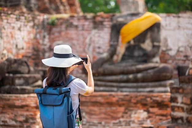 Une jeune femme se promène dans le vieux temple de phra nakhon si ayutthaya, en thaïlande, pendant une journée de détente. Photo Premium