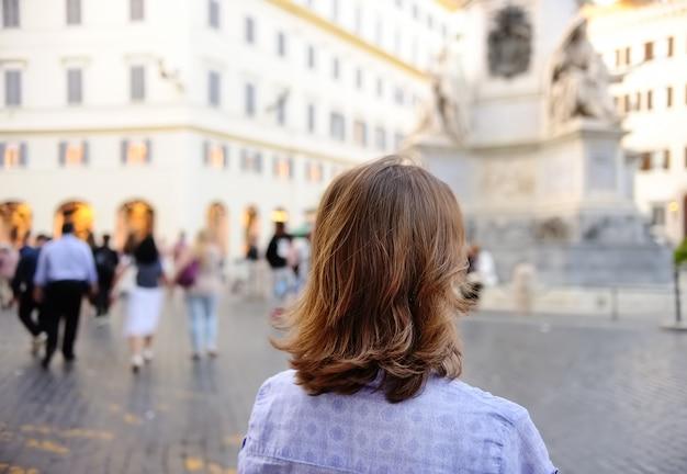 Jeune femme se promène sur la place à rome. Photo Premium