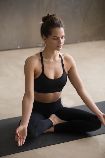Jeune femme séduisante assise dans une pose facile, studio gris Photo gratuit