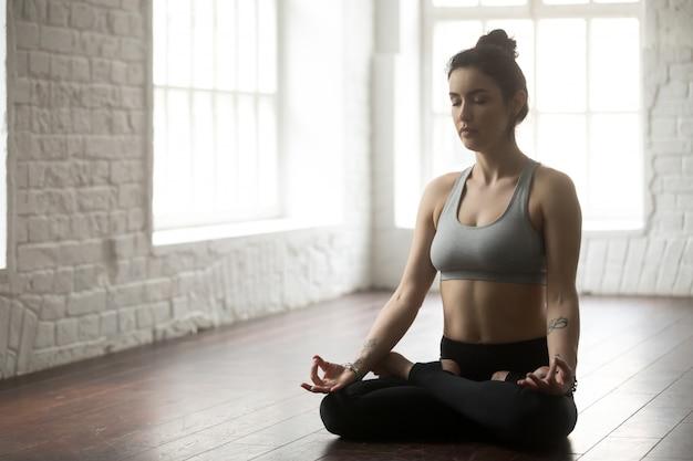 Jeune femme séduisante assise en posture de lotus, studio loft blanc Photo gratuit