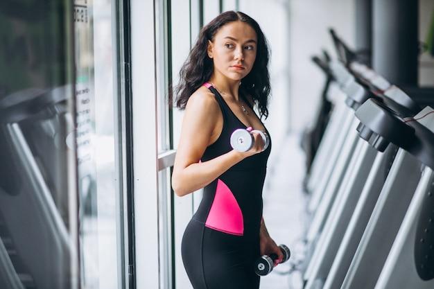 Jeune femme séduisante au gymnase avec des haltères Photo gratuit