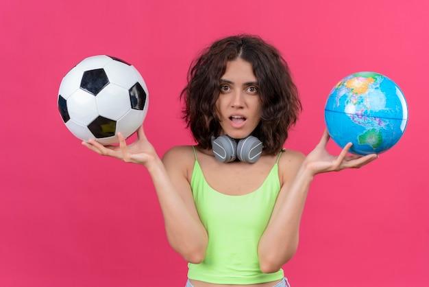 Une Jeune Femme Séduisante Aux Cheveux Courts En Vert Crop Top Dans Les écouteurs Tenant Globe Et Ballon De Football Photo gratuit