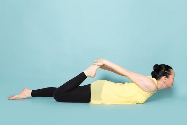Jeune Femme Séduisante En Chemise Jaune Et Pantalon Noir Faisant Des Postures De Yoga Photo gratuit