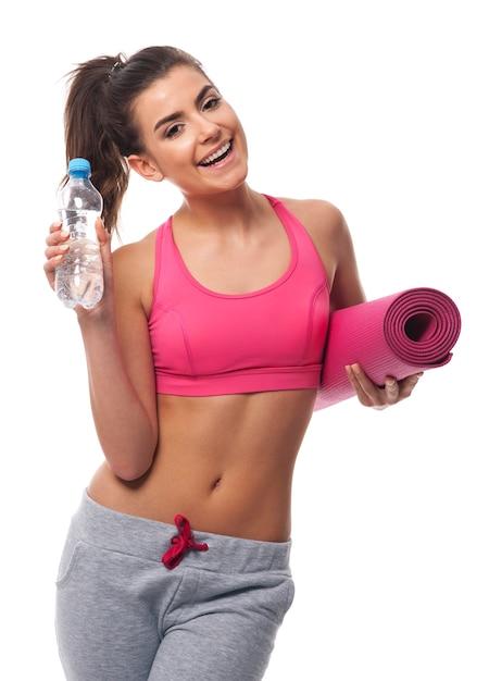 Jeune Femme Séduisante Avec De L'eau Et Tapis D'exercice Photo gratuit