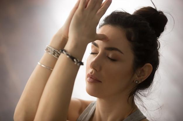 Jeune femme séduisante faisant namaste avec les yeux fermés Photo gratuit