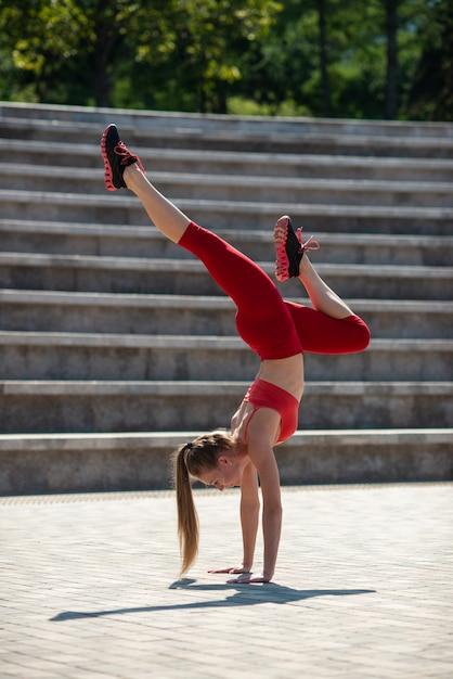 Jeune femme séduisante, pratiquer le yoga en plein air. la jeune fille effectue le poirier à l'envers Photo Premium