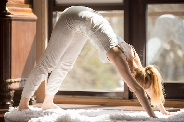Jeune femme séduisante yogi en posture adho mukha svanasana Photo gratuit