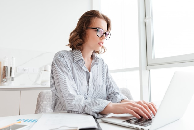 Jeune Femme Sérieuse En Chemise Rayée En Tapant Un E-mail à Son Patron Tout En étant Assis Sur Le Lieu De Travail Dans Un Appartement Lumineux Photo gratuit