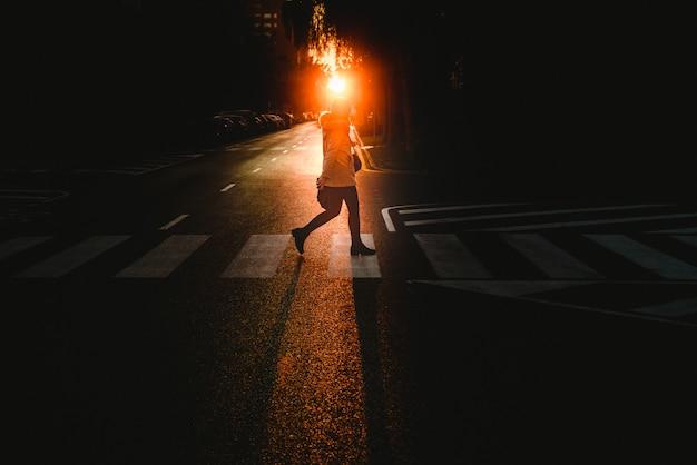 Jeune femme seule marchant et traversant une rue isolée par un passage piéton au coucher du soleil Photo Premium