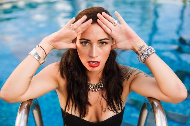 Jeune femme sexy posant dans une piscine en maillot de bain noir Photo Premium