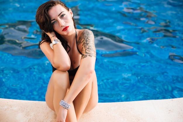 Jeune femme sexy près de la piscine en maillot de bain noir Photo Premium