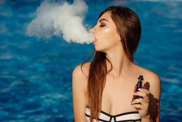 Jeune Femme Sexy Vapote Dans La Piscine. Un Nuage De Vapeur. Femme Chaude Et Sexy Vapotant (fumant Une E-cigarette) Sur L'eau. Vue Rapprochée. Concept De Vapotage Photo Premium