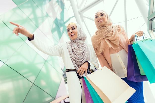 Jeune femme avec shopping au centre commercial avec un ami. Photo Premium