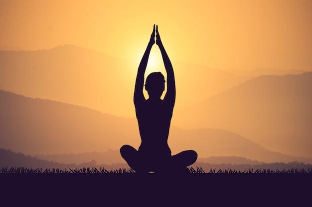 Jeune femme silhouette, pratiquer l'yoga sur le muontain au coucher du soleil. couleur vintage Photo Premium