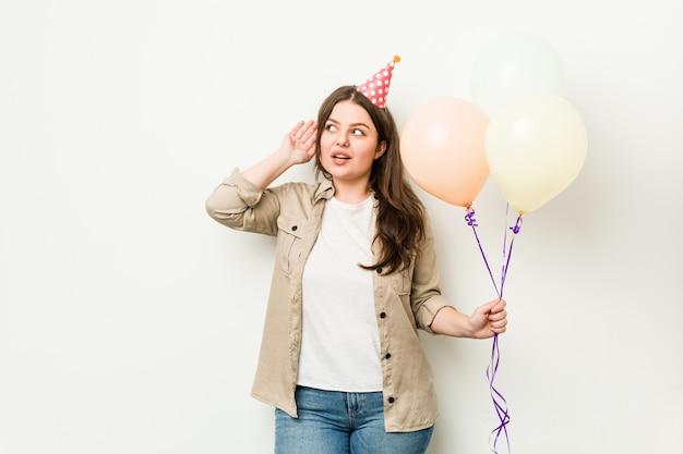 Jeune Femme Sinueuse De Taille Plus Fête Son Anniversaire En Essayant D'écouter Un Potin. Photo Premium