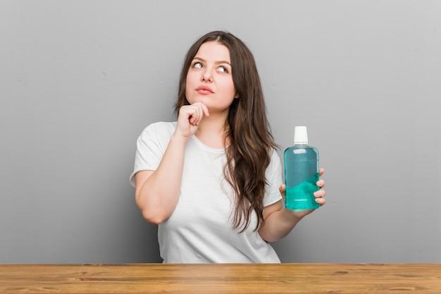 Jeune Femme Sinueuse De Taille Plus Tenant Un Rince-bouche à Côté Avec Une Expression Douteuse Et Sceptique. Photo Premium