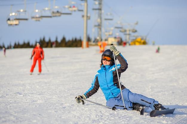 Jeune femme skieuse après la chute sur une pente de montagne Photo Premium